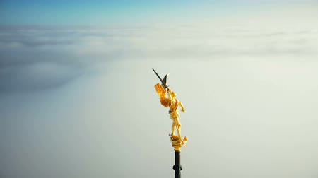 michael : Super close-up aerial shot, golden St Michael statue on top of Mont Saint Michel castle fortress spire above cloudy sky.