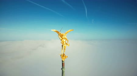 irreal : Amazing aerial close-up shot of golden St Michael angel statue on top of famous Mont Saint Michel castle spire in sky. Stock Footage