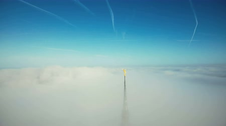 normandiya : Drone flying away from epic golden angel statue on top of Mont Saint Michel castle steeple above the clouds in the sky. Stok Video