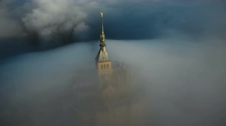 irreal : Drone flying above sunrise Mont Saint Michel castle steeple covered by thick fog clouds flowing into mystic darkness.