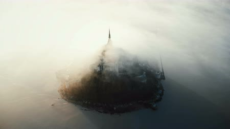 irreal : Drone flying around famous Mont Saint Michel, ancient island fortress castle hidden by thick foggy mist flow on sunrise.
