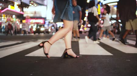 haklar : Slow motion lifestyle shot of beautiful young female legs walking across crowded street at night in Times Square, NY.