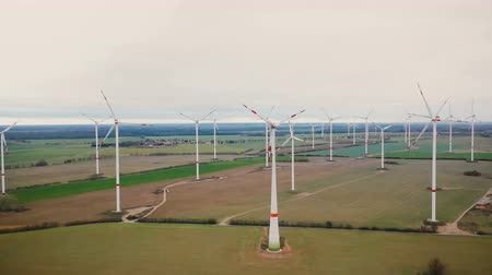 malom : Drone panning right along large windmill turbine farm generating eco-friendly renewable power in cloudy autumn field.
