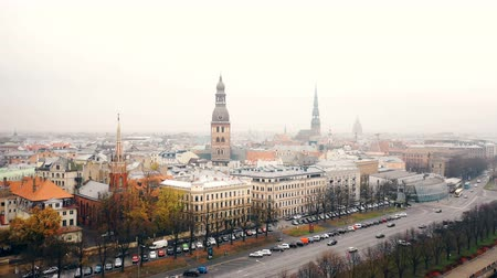 latvia : Beautiful aerial skyline panorama of Riga old town and Dome Cathedral, car traffic at Daugava river on foggy autumn day. Stock Footage
