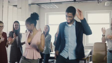 inspiradora : African American male and female employees doing funny ethnic dance moves at office party with multiethnic colleagues 4K Vídeos