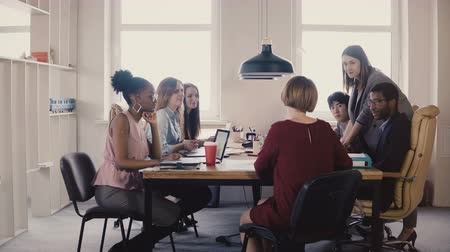 medezeggenschap : Happy female business coach gives guides to employees. Multiethnic teamwork by the table at office board meeting 4K. Stockvideo