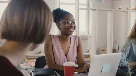 medezeggenschap : Happy African American female employee sitting by the table at team meeting. Multiethnic teamwork in modern office 4K.