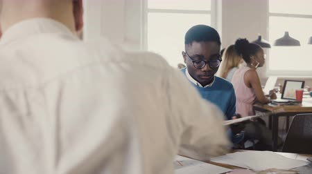 işbirliği yapmak : Concentrated African American young man working hard on architecture sketch with colleagues in trendy office space 4K. Stok Video
