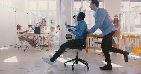 amalucado : Slow motion crazy fun young black businessman riding office chair, celebrating success with team throwing paper in air.
