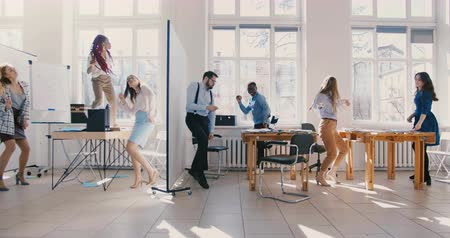buta : Slow motion dolly shot of business people dancing in light modern office party, multiethnic team celebrating success.