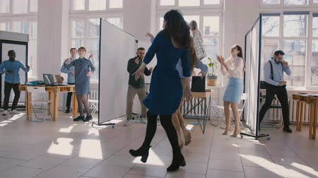 doorbraak : Two young fun female office colleagues dancing together with multiethnic company staff celebrating success slow motion.
