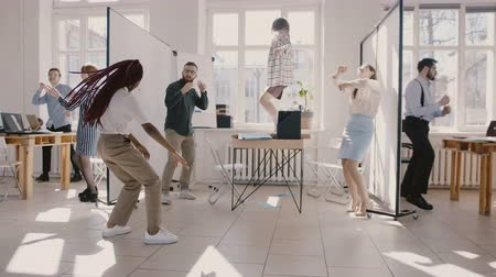 career success : Happy young black female office worker dancing with colleagues at wild fun workplace celebration party slow motion.