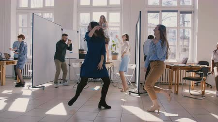 femminismo : Two happy female business company partners doing fun winner dance celebrating together with colleagues slow motion.