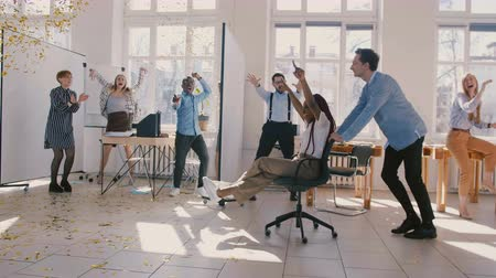 luck : Slow motion black businesswoman celebrates promotion riding winner chair under falling confetti, colleagues clapping. Stock Footage