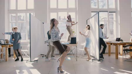 doorbraak : Young happy Caucasian female boss dancing in modern office celebrating together with multiethnic colleagues slow motion.