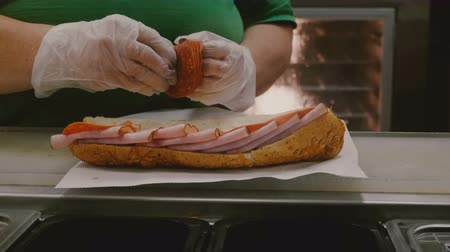 sekaná : The process of making a big king size meat sandwich with ham and salami. Human hands lay out ingredients on large bread.