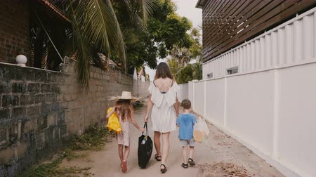 klusjes : Happy young mother walks together with two little children carrying shopping bags towards home along little narrow alley Stockvideo