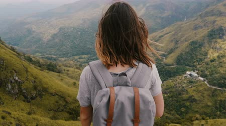 pensamiento positivo : Medium back view shot, young happy woman hiking with backpack and flying hair watching incredible mountains in Sri Lanka