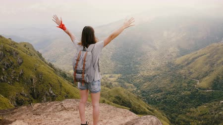 pensamiento positivo : Camera pans up behind young happy tourist woman with backpack raising arms wide into the air at epic mountains Sri Lanka