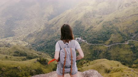 magas szög : Back high angle view happy tourist woman with backpack touching hair at stunning mountain scenery view in Sri Lanka.