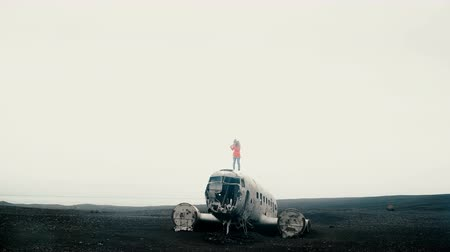 yansıtıcı : Young woman in pink jacket standing on the top of the crashed DC-3 BMC in Iceland and looking around of black beach. Stok Video