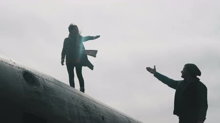 amigos : Young woman standing on the top of crashed DC-3 plane in Iceland and reaching out the hand to man standing near. Stock Footage