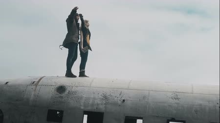 think big : Young traveling couple standing on the top of crashed DC-3 plane in Iceland and raising hands together in windy day. Stock Footage