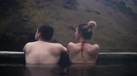 geotermální : Back view of young couple washing in hot springs in Iceland. Traveling man and woman relaxing in mountains valley.