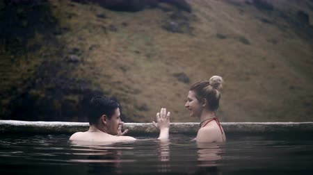 molas : Young couple relaxing in hot springs in Iceland. Traveling man and woman swimming in mountains valley, romantic date.