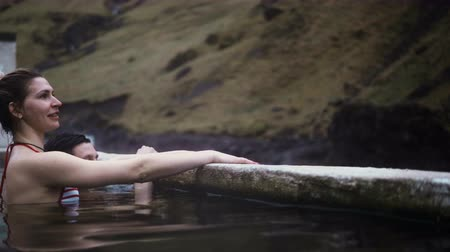 rugók : Young happy couple swimming in hot springs in Iceland. Traveling man and woman enjoying the view in mountains.