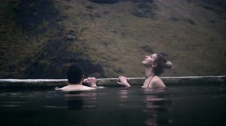 bagno di vapore : Young loving couple swimming in hot springs together. Man and woman relaxing at water in mountain valley in Iceland.