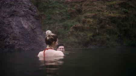 fürdés : Young happy woman swimming in the hot springs together. Traveling man and woman in mountains valley in Iceland.