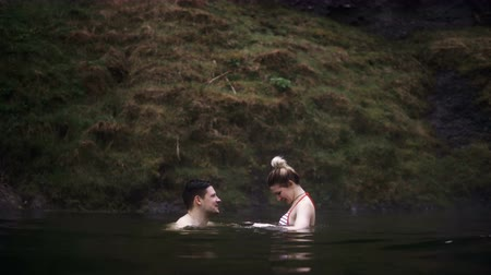molas : Young beautiful couple having fun together during the swimming. Man and woman in hot springs in Iceland.