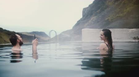 geotermální : Young happy couple resting in hot springs in Iceland. Handsome man taking photos on smartphone of woman.