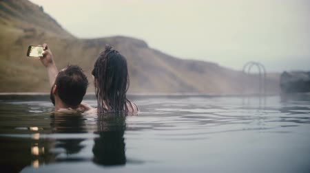 geotermální : Young couple taking selfie photos on smartphone in mountains valley. Man and woman swimming in hot springs in Iceland.