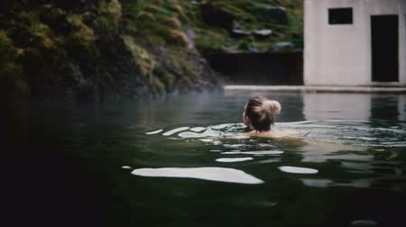 çare : Young beautiful woman swimming in hot spring in Iceland. Blonde female enjoying the rest in mountains valley. Stok Video