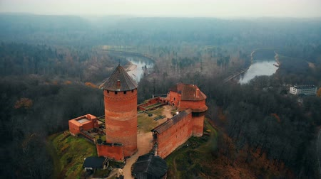 latvia : Drone flying low over ancient Turaida castle and museum reserve in Sigulda, Latvia, autumn foggy forest and river view.