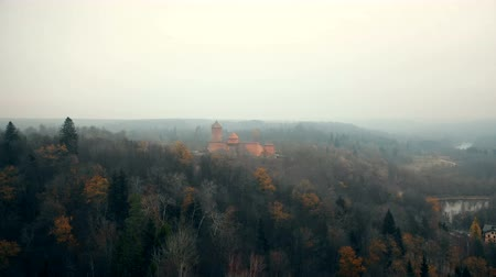 Латвия : Drone flying towards ancient Turaidas castle and museum in Sigulda national park reserve, autumn foggy forest in Latvia.