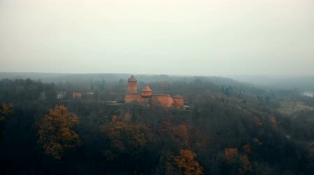 Латвия : Beautiful aerial shot of mysterious ancient Turaida castle museum in Sigulda national park reserve foggy forest Latvia.