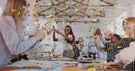 alkalmazottak : Confident African American businesswoman celebrates success with confetti, happy young multiethnic team at meeting. Stock mozgókép