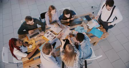 анализ : Top view business people group work together on meeting with male boss and female expert coach in modern light office. Стоковые видеозаписи