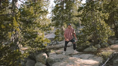 kalifornie : Beautiful view of young handsome happy man jumping down on big rocks while hiking alone at Yosemite park slow motion.