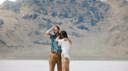 цели : Happy attractive romantic couple stand together hugging, kissing at epic white flat salt desert of Bonneville Utah.