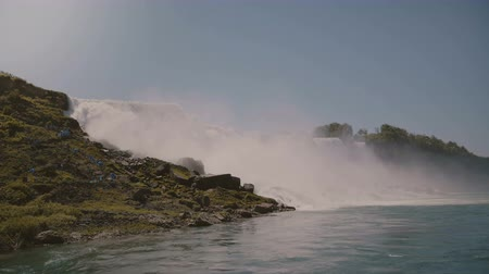 бросаясь : Cinematic shot of tourists in raincoats watching epic wall of water at beautiful famous Niagara waterfall on sunny day. Стоковые видеозаписи