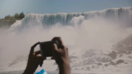 fotoğrafçı : Slow motion close-up human hands taking smartphone photos of epic Niagara Falls waterfall panorama on a clear summer day Stok Video