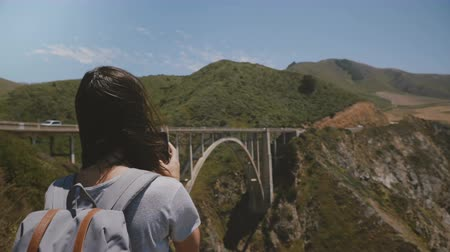průhled : Back view young traveler woman hiking with backpack takes smartphone photos of epic scenery at famous Bixby bridge.