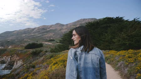 positive vibes : Camera follows young happy woman walking on small yellow flower path towards rocks and forest at Big Sur coastline.
