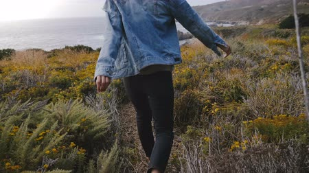 positive vibes : Camera follows young happy woman walking among yellow flowers and dry plants to amazing rocks on Big Sur ocean coastline