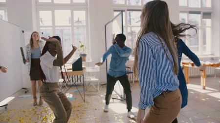 motivados : Camera moves around young multiethnic business group celebrating success dancing at fun workplace party slow motion.