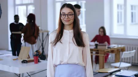 attorney : Medium portrait of beautiful young smart brunette business woman in eyeglasses looking at camera in trendy loft office.